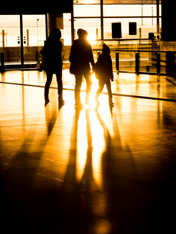 Silhouette family in international airport preparing for departure