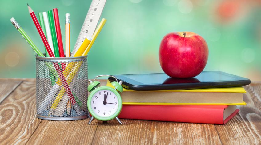 Materiali scolastici su tavolo di legno con natura viva e una sveglia che evoca il tempo