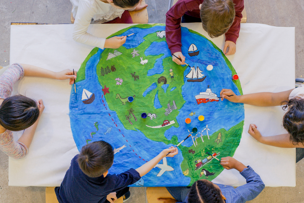 An aerial view of a multi ethnic group of children painting the globe and it's animals, fish, and vehicles. One girl paints a steam boat, while a boy colours in the ocean.